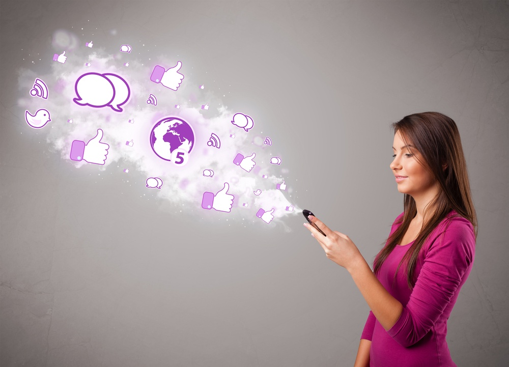 Pretty young girl holding a phone with social media icons in abstract cloud.jpeg